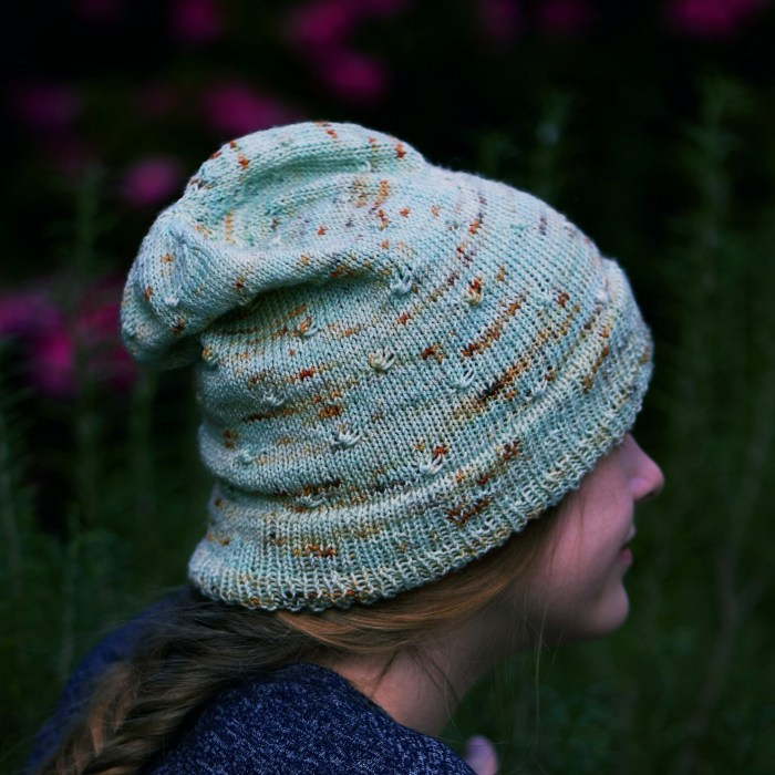 a slouchy handknit minty green hat with orange specks featuring staggered knot stitches