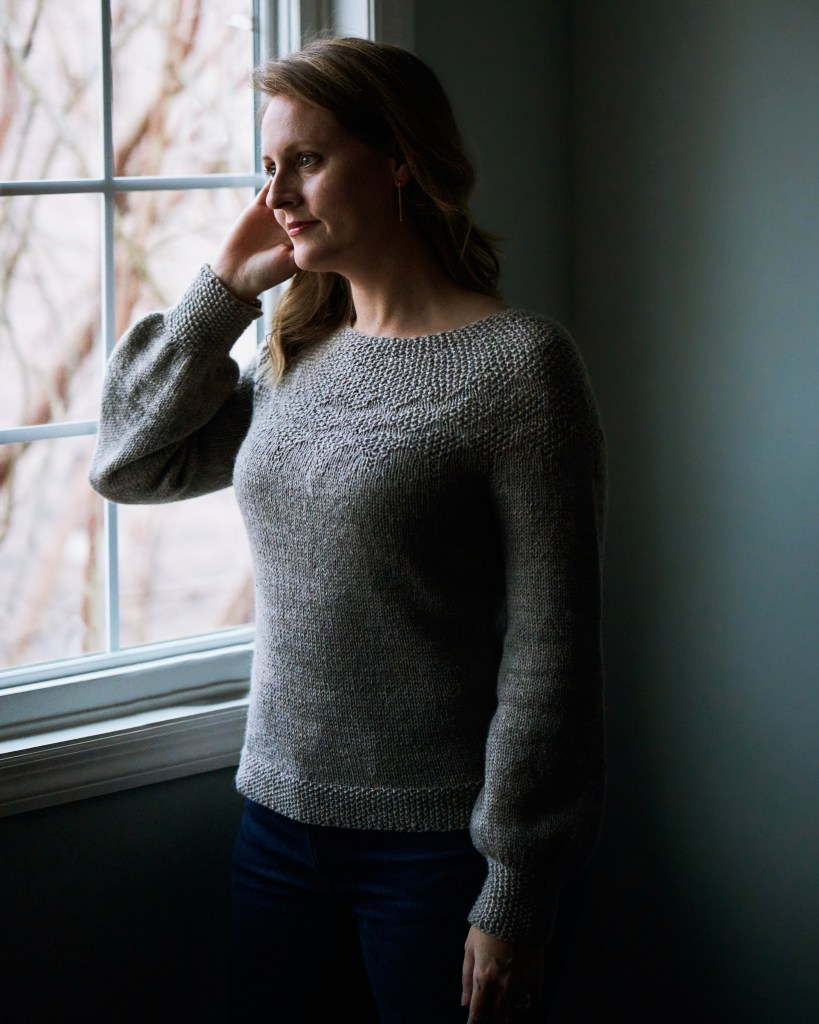 Jamie is wearing a gray Birdseed sweater that features lots of seed stitch and gazing out the window.