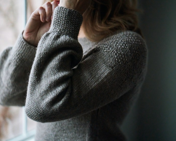 Closeup of the arms of a gray hand knit sweater. The arm are both bent upwards with the hands almost together. Seed stitch at the shoulder and cuffs can be seen.