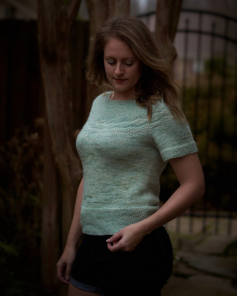 Side view of Jamie wearing a minty green hand knit sweater with short sleeves and seed stitch at the yoke, hem and cuff.
