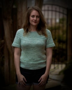 Jamie wearing a minty green hand knit sweater with short sleeves and seed stitch at the yokel hem and cuffs.
