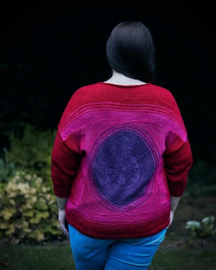Back view of a red and purple handknit sweater modeled
