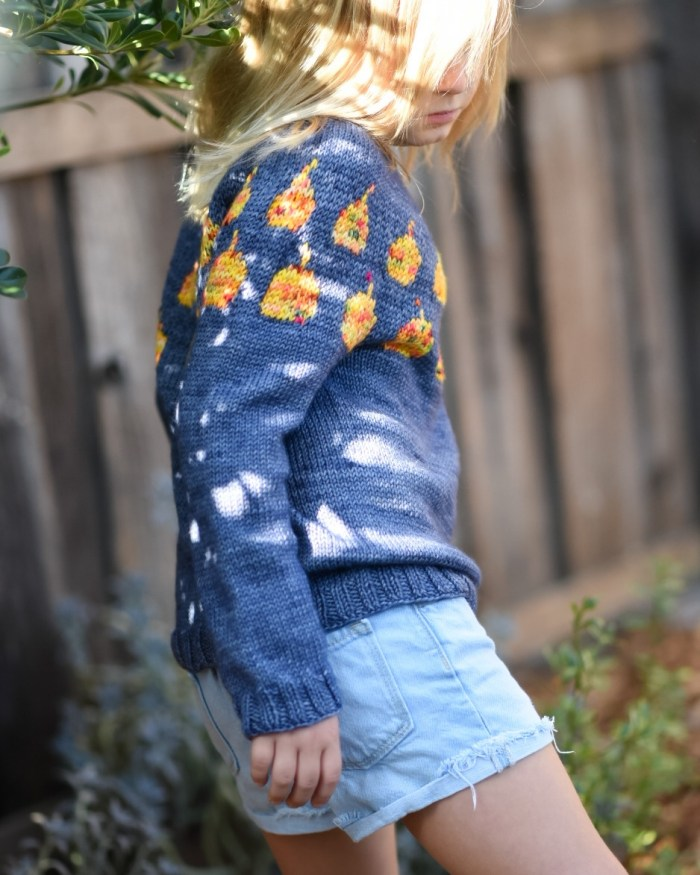 An 8 year old girl wears a gray handknit pullover with orange pumpkins in the yoke