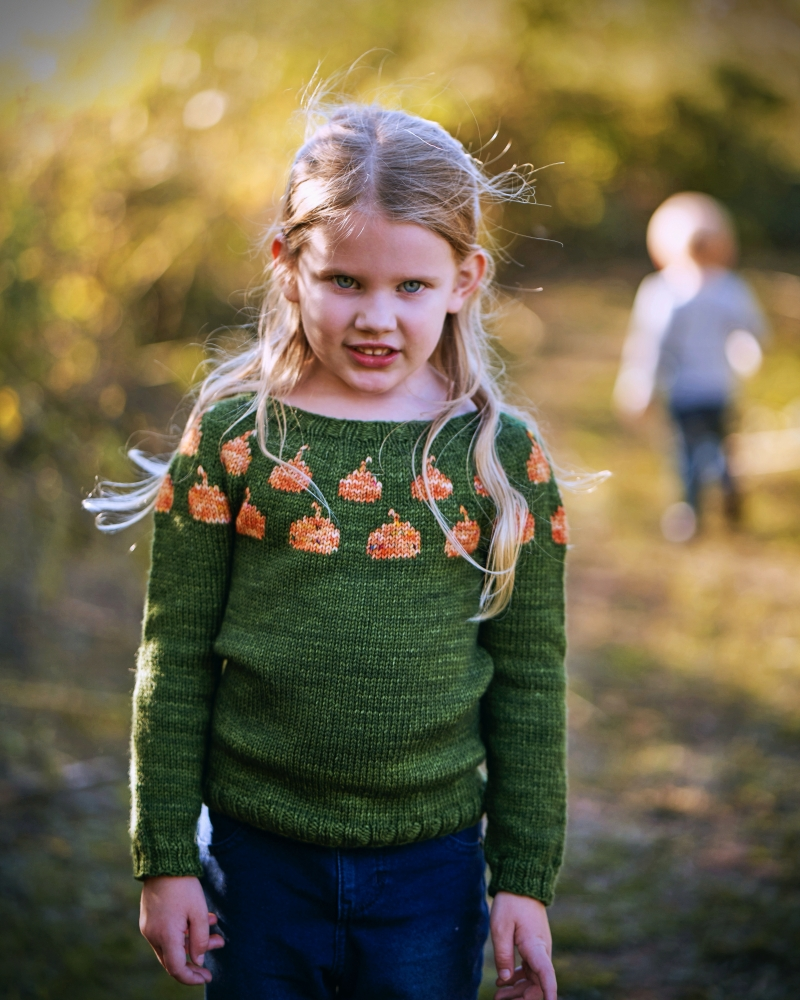 A 6 year old girl wears a green handknit pullover with orange pumpkins in the yoke