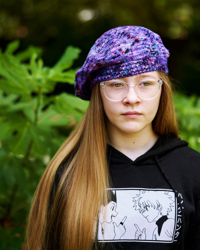 A girl with clear glasses and long dark blonde hair wears a purple handknit beret
