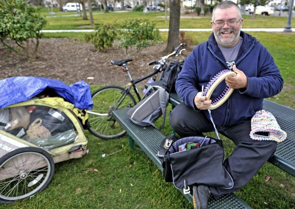 Homeless man loom knits hats for others in need.