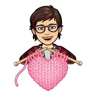Lea-Ann holding knitting needles making a pink heart.