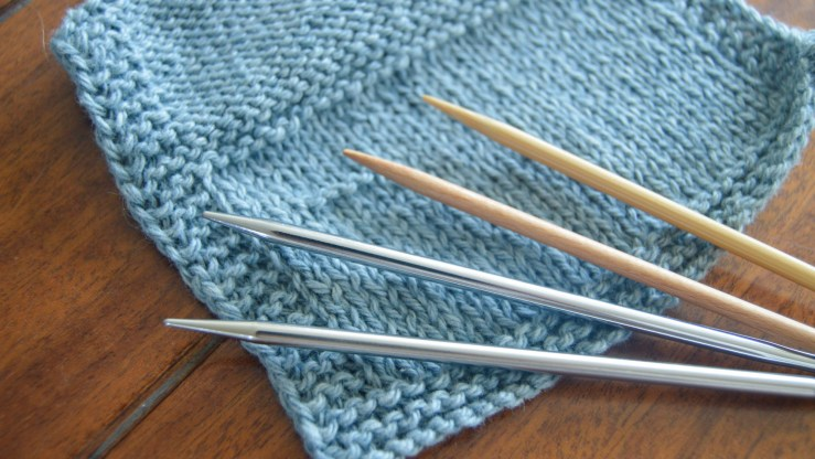 A knitted gauge swatch and knitting needles: A pair of stainless steel needles and a pair of birch wood needles.