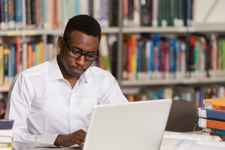 Man using laptop in library
