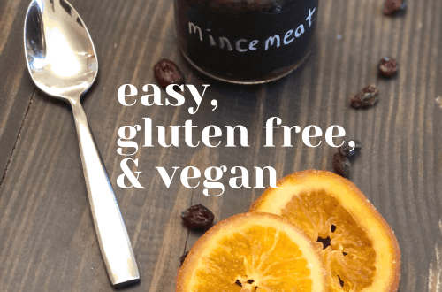 Easy gluten free vegan mincemeat pie filling from knowgluten.me in a small jar on a table with candied orange slices, raisins, and a spoon