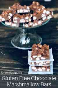 Chocolate marshmallow bars on a serving tray with a stack of marshmallow bars in front.