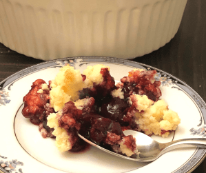 Cherry cobbler on a plate with a spoon, sized for Facebook.
