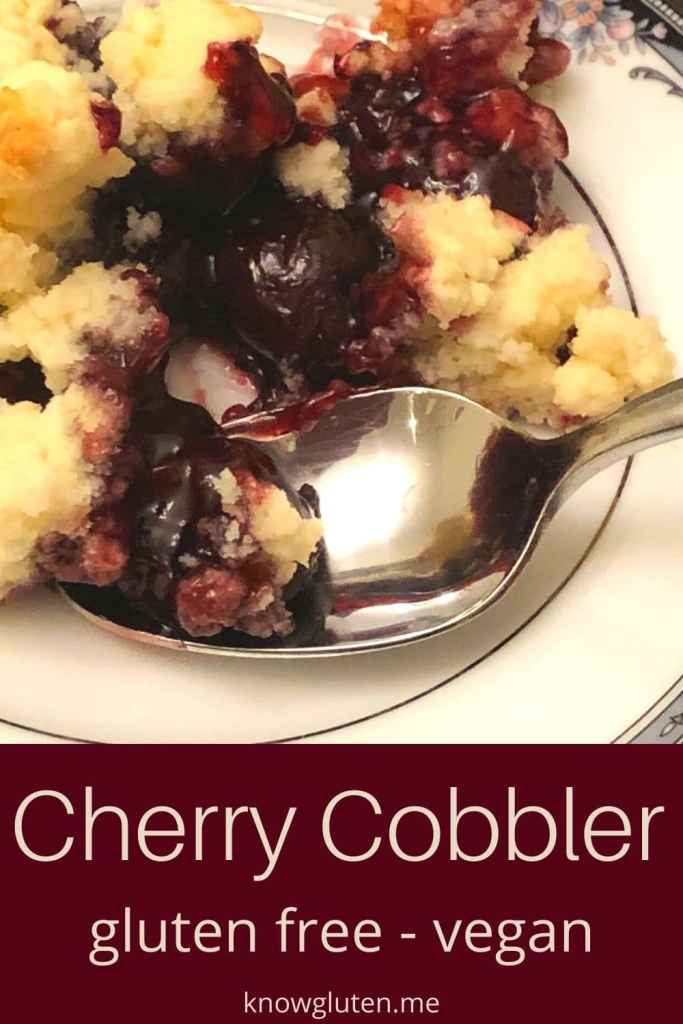 A closeup of gluten free cherry cobbler on a china plate with a spoon.