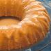 A closeup of a gluten free vanilla bundt cake with a glaze on a glass serving tray.