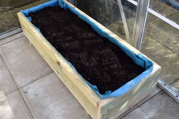 Fill with compost to just below the rim of the box