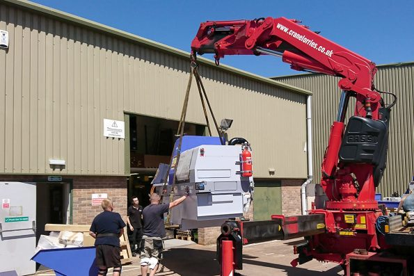 The lathe being craned into the workshop