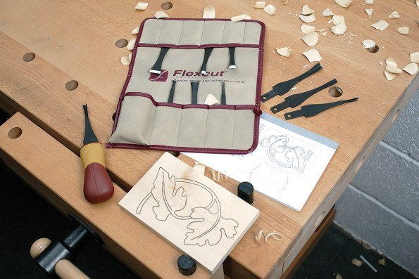 Flexcut carving kit on workbench with template and wood held in a vice