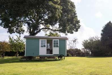 A completed Shepherds hut in an orchard