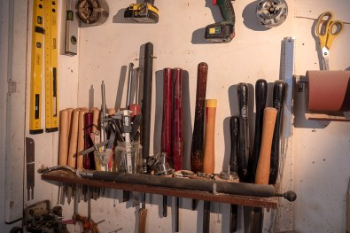 woodturning tools hung up on the wall of the workshop