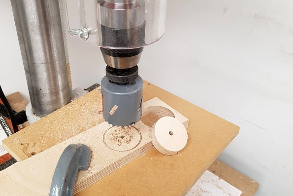 Using a hole saw in a pillar drill to cut out the wheels