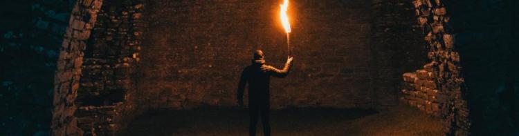 Man with a torch looking aty a wall in a dark dungeon.