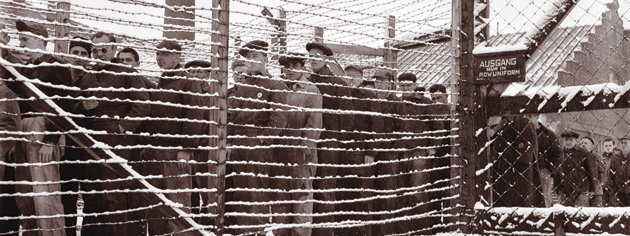 Prisoners look out from behind barbed wire at Sherbrooke, Que., in 1945.