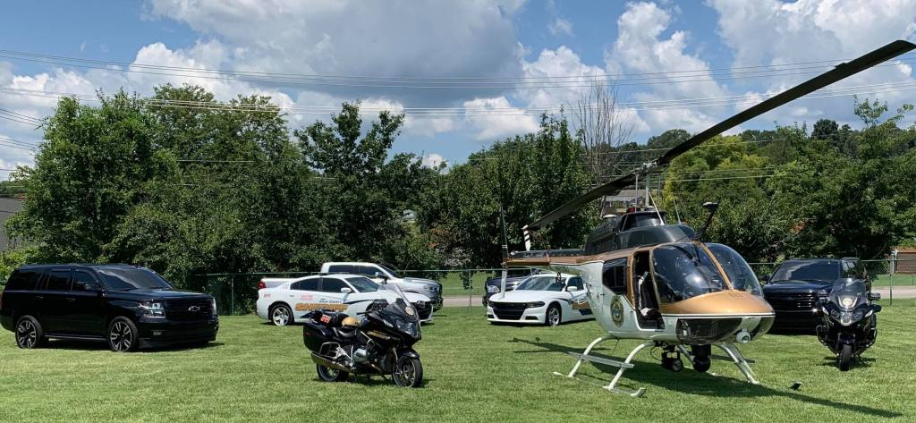 KCSO cruisers, SUVs, motorbikes, and helicopter parked on grass