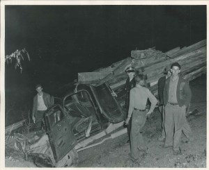 Black and white image of officer and other men inspecting a wrecked truck