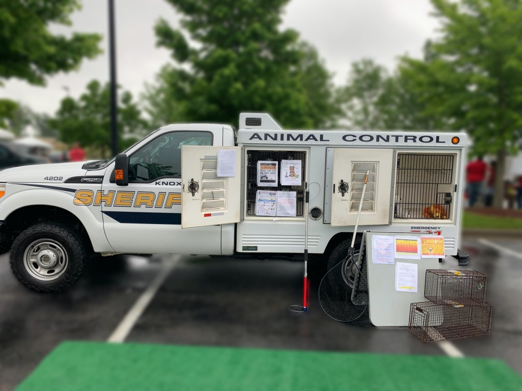 Animal control truck with open compartments