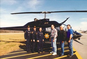 Several officers posing next to KCSO helicopter
