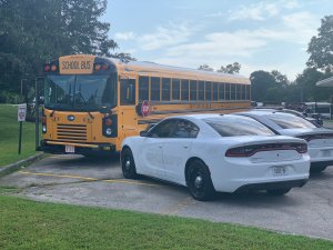 Unmarked KCSO cruisers parked next to school bus