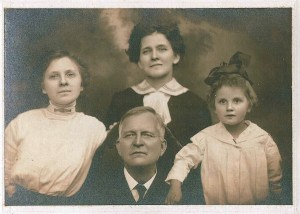 Black and white image of man sitting with woman and two girls