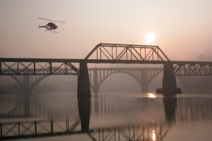 KCSO helicopter flying over river with bridges
