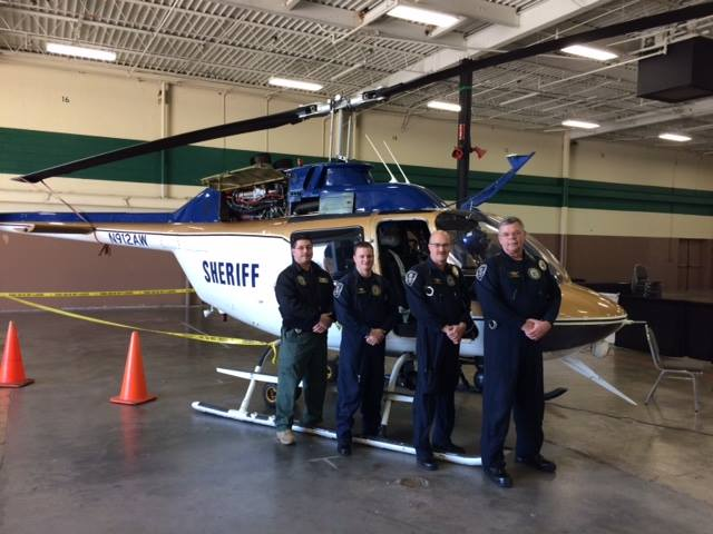 KCSO Aviation officers standing next to helicopter in hangar