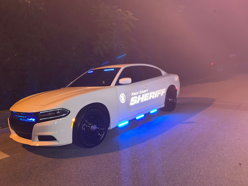 Unmarked KCSO Challenger with emergency lights lit at night