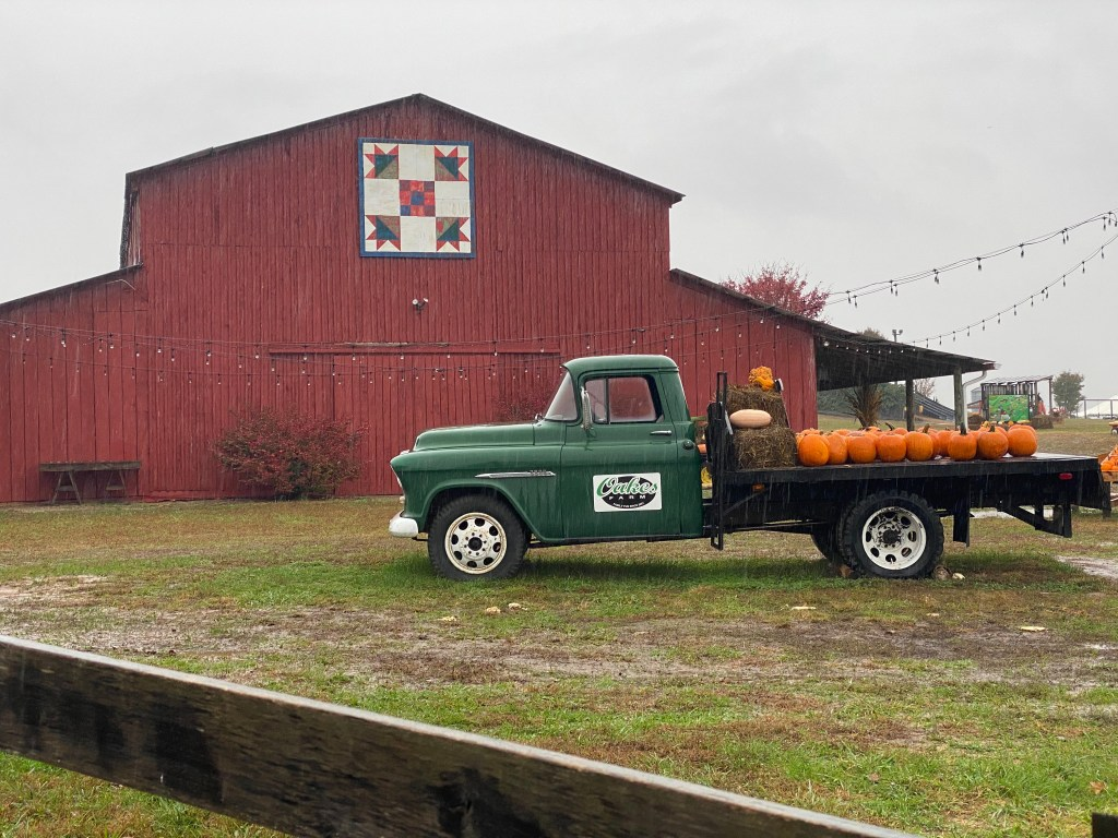 Red barn and green truck with pumpkins on bed