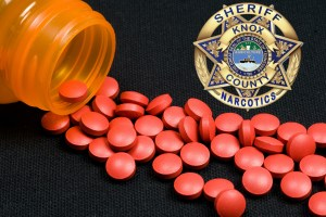Pill bottle with pills spilling out and KCSO badge overlay