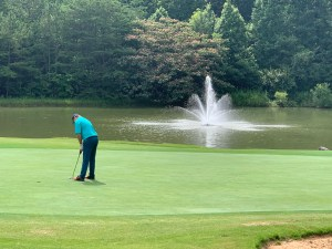 Golfer on course near a pond with fountain