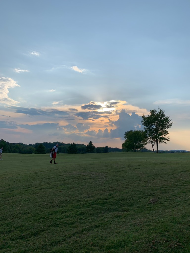 Golf course with player near sunset