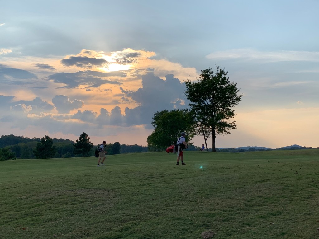 Golf course with players near sunset