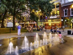 Market square fountains with kids playing and people watching