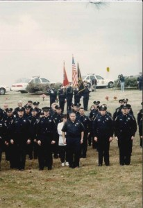 Officers standing at attention with flags