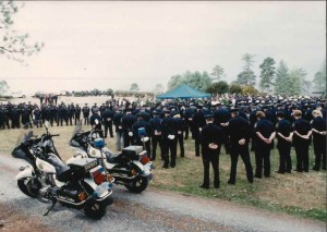 Many officers having moment of silence at funeral with two Sheriff motorbikes nearby