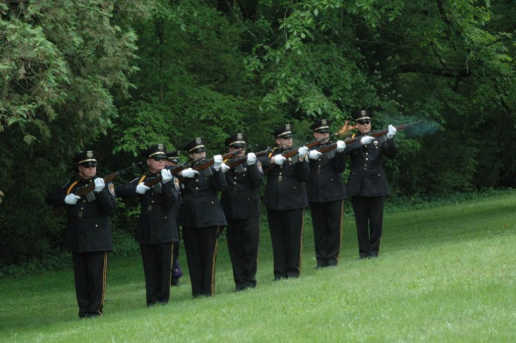 7 Honor guard members with rifles firing
