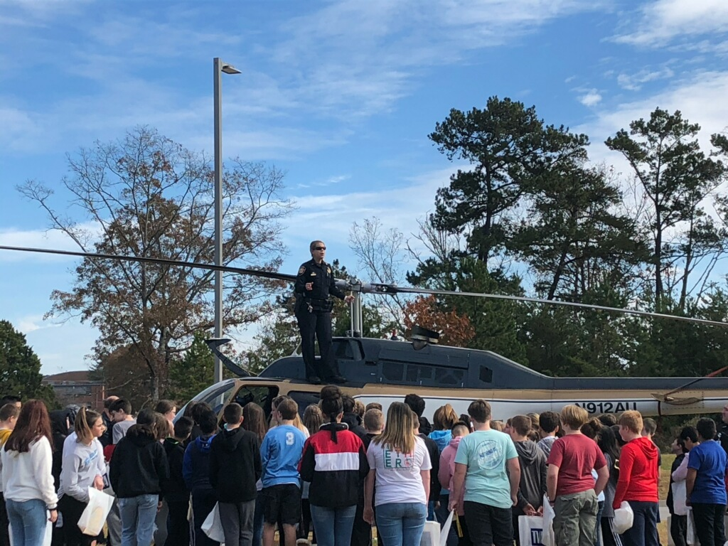 Female officer standing on top of parked KCSO helicopter talking to group of children
