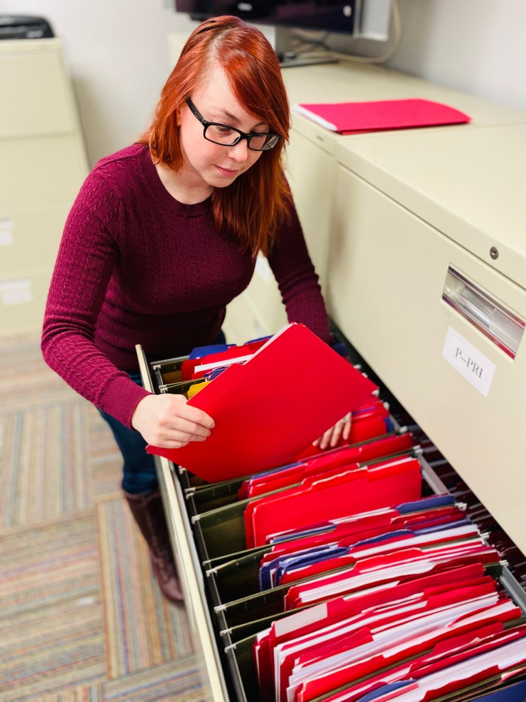 Female getting folder out of filing cabinet