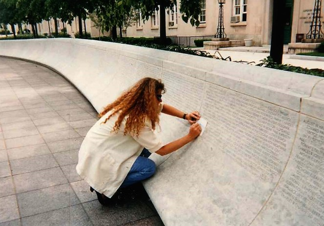Deputy Kennedy's wife penciling his name onto paper from memorial wall