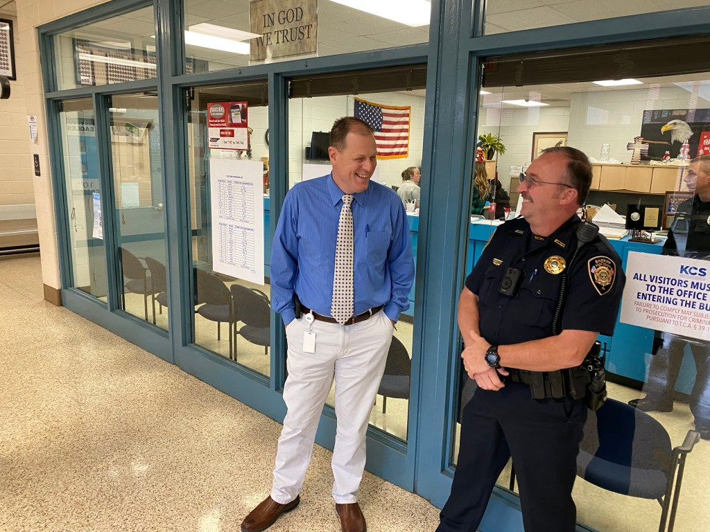 KCSO officer and teacher standing and laughing next to school office