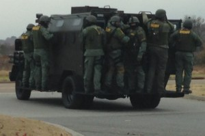 SWAT officers in full gear riding on outside of SWAT vehicle