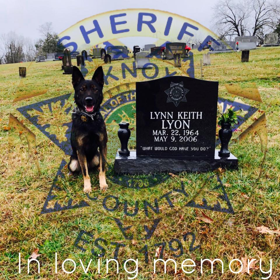 K9 sitting next to Keith Lyon's tombstone with badge background